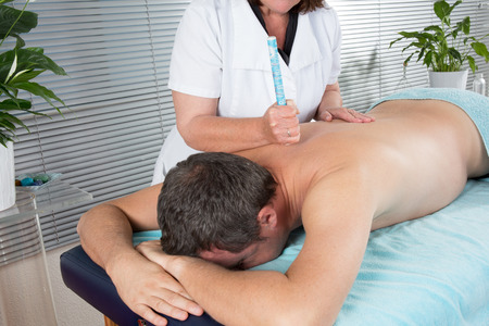 Female therapist in chinese medicine working on the back of a  man