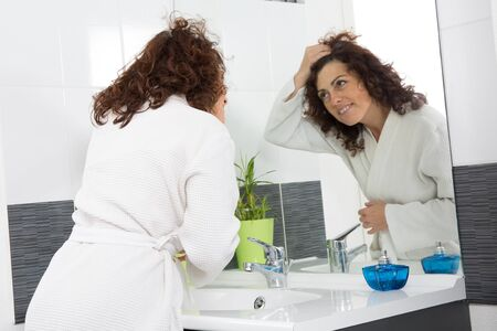 beautycare: Woman looking at her hair worried by hair getting grey Stock Photo
