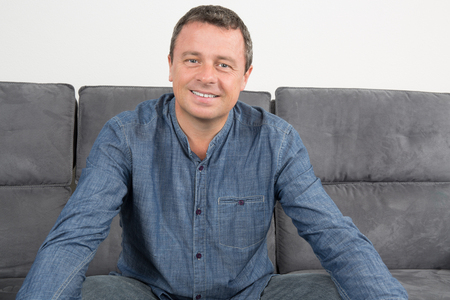 40 year old man: Handsome and smiling man sitting in couch at home Stock Photo