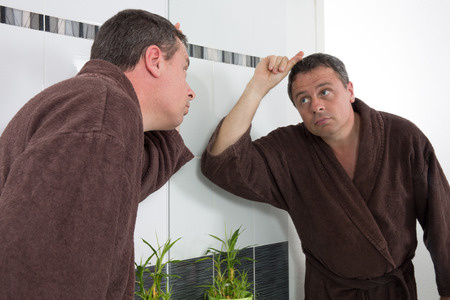 40 year old man: Middle-aged man in bathroom applying facial lotion