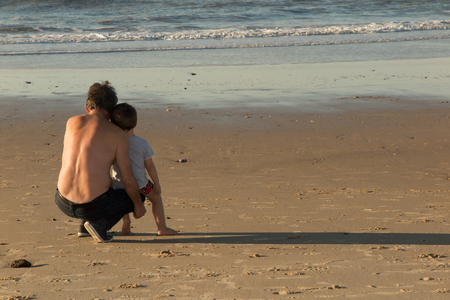 grand sons: Rear view of a father with his son at the beach future concept