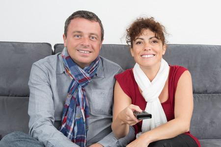 pareja viendo tv: Feliz pareja viendo la televisi�n en su casa en el sof� Foto de archivo