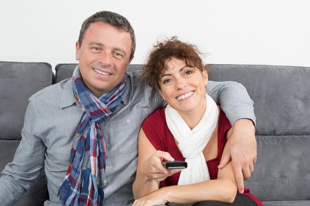 pareja viendo tv: Feliz pareja viendo la televisión en su casa en el sofá Foto de archivo