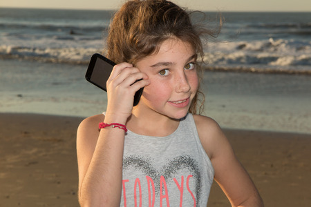 looking at viewer: Caucasian pre-teen girl on beach looking at viewer. Stock Photo