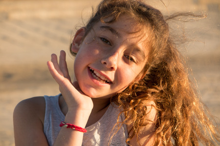 looking at viewer: Caucasian pre-teen girl on beach looking at viewer