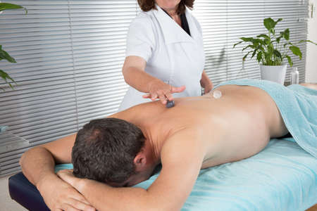 clairvoyant: Male laying on chest with stone treatment on back Stock Photo