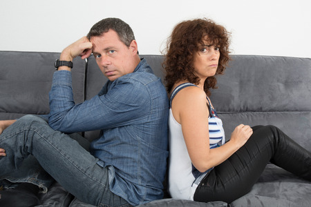 fatigued: Bored couple sitting on the couch at home