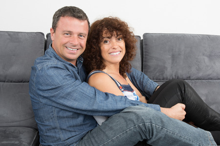 uninterested: Bored couple sitting on the couch at home