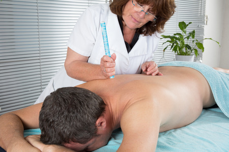 moxibustion: Female therapist in chinese medicine working on the back of a  man