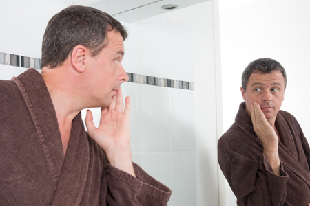 beautycare: Middle aged man in front of mirror applying cosmetics