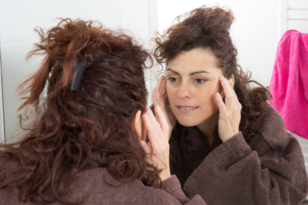 Middle-aged woman applying comestics on her face