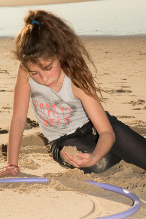 10 12 years: Young and pretty girl playing in the sand at the beach summertime Stock Photo