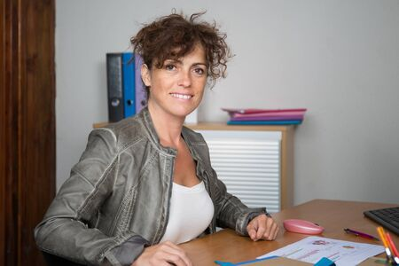 40 year old woman: Smiling office worker sitting at desk Stock Photo
