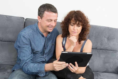 cocooning: In love couple using a tablet computer in their living room