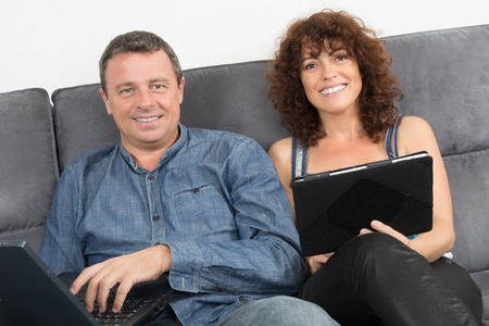 couple on couch: Loving couple using a digital tablet on couch at home Stock Photo