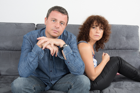dispirited: Bored couple sitting on the couch at home