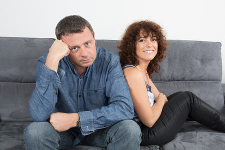 disinterested: Bored couple sitting on the couch at home
