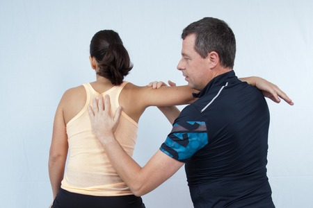 strength therapy: Chiropractor examining a charming womans back in a room