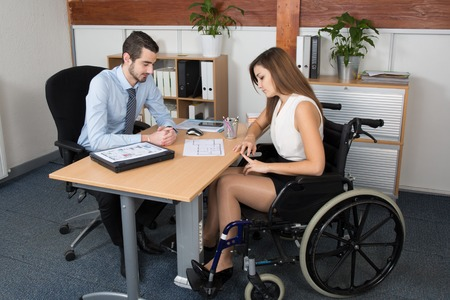 Young woman in wheelchair working with a male colleague at work