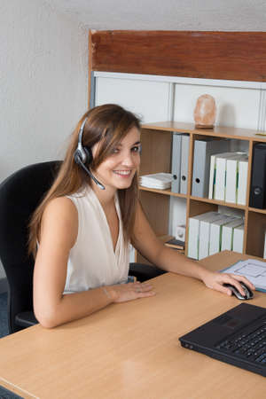 dispatcher: Attractive young dispatcher working in bright office, sitting at desk, smiling. Stock Photo