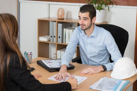 building planners: Happy and charming Young woman Discussing with consultant in office Stock Photo