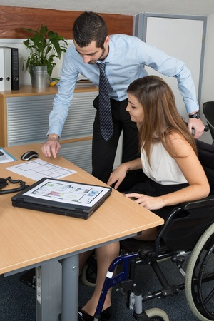 paraplegico: Handicapped woman attending a meeting in a bright office