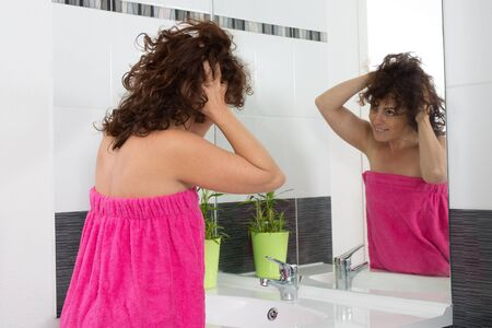 beautycare: Woman worried by hair getting grey and looking at the hair Stock Photo