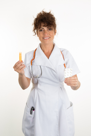 doctor holding pills: Vertical image of a female doctor holding pills and homeopatic granule isolated