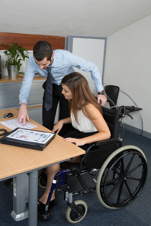 wheelchair users: Young and gorgeous woman in wheelchair working with a male colleague