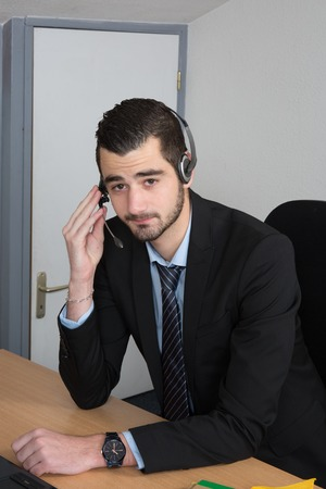 sales rep: Handsome man wearing a headset and taking a call from a customer at work