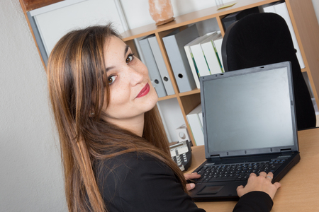 female lawyer: Rear view of a young brunette in a suit working on a laptop computer at her office Stock Photo