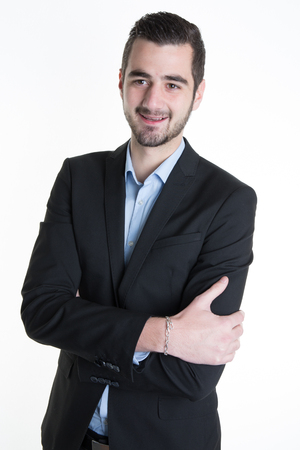 confidently: Handsome young businessman standing arms crossed, smiling confidently. Stock Photo