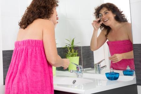 crimping: Serious Woman Crimping her Right Eyelashes Using Lash Curler