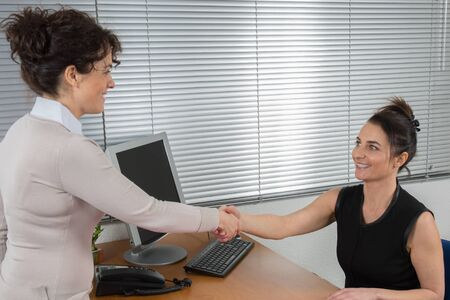 concluding: Two businesswomen at a desk shaking hands on concluding a deal
