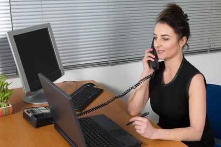 office women: Happy office girl at desk working on desktop computer, using landline phone, smiling