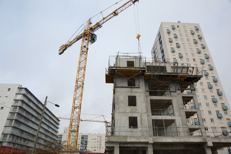 Building and cranes under construction against grey sky