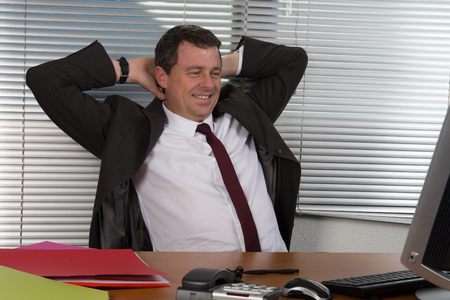 relaxed business man: Relaxed  business man happy smile sitting at the desk, handsome businessman relaxing hold hand on head look up