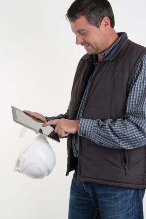 clothes organizer: Cheerful worker in white helmet and brown waistcoat holding shockproof digital tablet in both hands.