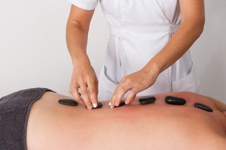 hot stone: Man having a hot stone massage at a beauty center