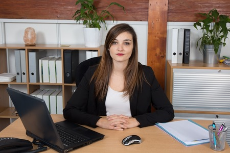 lovely businesswoman: Serious lovely businesswoman presenting notebook sitting at her desk looking at camera