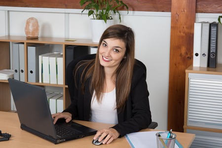 business suit: Woman. Girl. Business woman. Girl working with the laptop at office Stock Photo