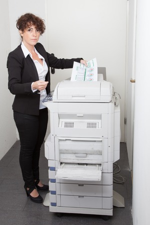 photocopy: Pretty young secretary using  photocopy machine in office