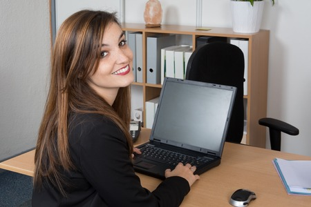 looking behind: Happy young businesswoman looking behind  working at office