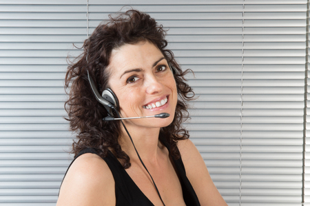 hands free phones: Smiling  happy business woman wearing a headset answering calls at a client service centre or wanting to communicate hands free while continuing to work in her office Stock Photo