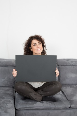 endorsing: Close up Sitting Young Woman Holding Black. Cardboard .Woman holding black cardboard while Looking at the Camera.