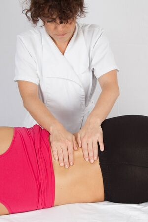 erector: Deep tissue massage on the womans middle back on erector spinae muscles at spa center