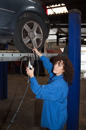 blue overall: Woman as female car mechanic working on an auto in a workstation