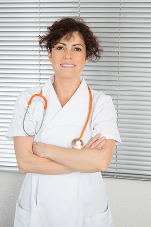 waist shot: Portrait of a smiling female doctor. Waist up studio shot on gray background. Stock Photo