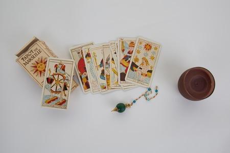 Tarot kaarten voor een fortuin -teller en slinger op wit wordt geïsoleerd Stockfoto
