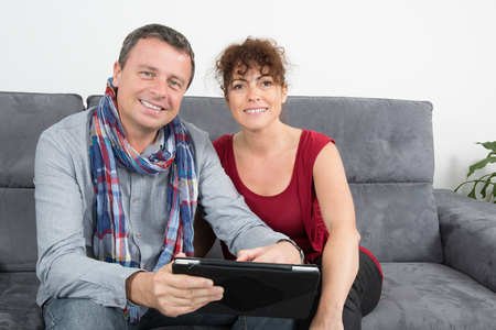 websurfing: Middle-aged couple websurfing on internet with touchpad
